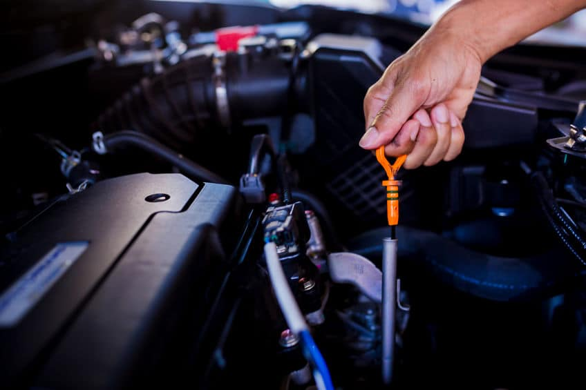 Check the oil level in car engine - mechanic checking car engine